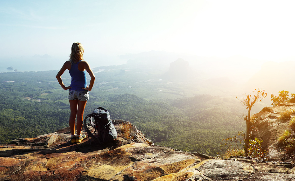 This is an image of a girl on top of a mountain