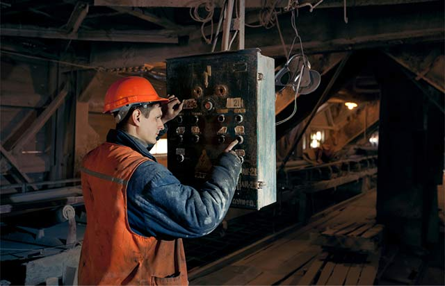 This is a picture of a electrican working on equipemnt in a mine